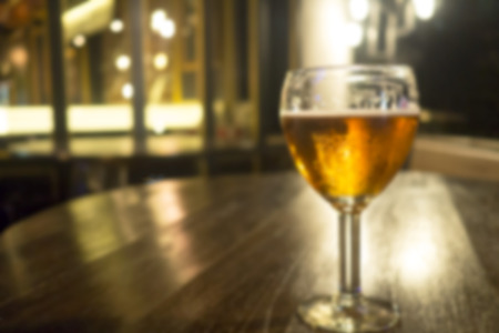lovelorn: Blurred vintage glass of light beer on wood table in a pub restaurant