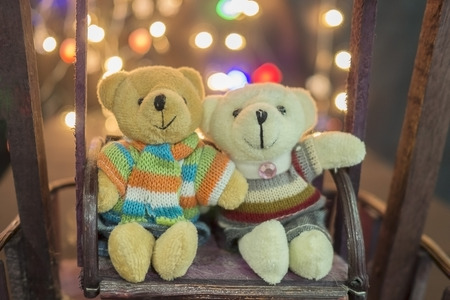 destiny: Cute two doll bears. Pair of cute teddies are sitting on wood swing with bokeh light in background. Teddies wear winter suite. Hug teddies. Concept of love, Valentine, soulmate, destiny.