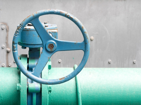 regulating: Blue old valve and old green pipe. Industrial water valve.