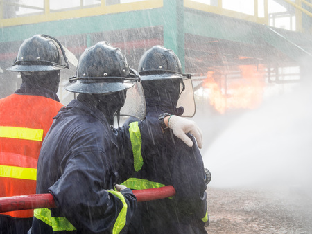 pressured: Firefighters fighting fire with pressured water during training exercise. Fire fighter spraying a straight steam into fire off. Stock Photo