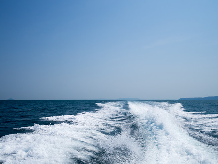 foamy: Restless foamy blue sea wake water on the sea water surface with clear blue sky while travel by speed boat in the ocean. Stock Photo