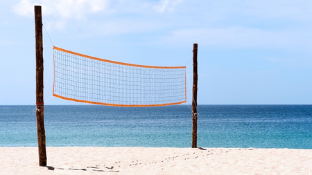 Volleyball net at beach. A volleyball net on beach with blue sea, clear and sunny sky. Stock Photo