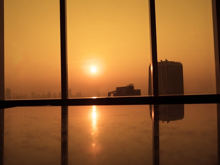 Sunrise morning. Silhouettes of glass window with orange sunrise background. View from high office building.