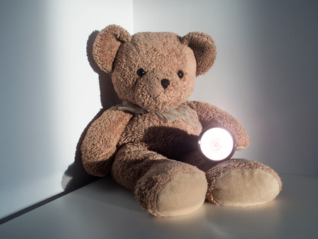 Cute bear holding flashlight sitting alone on wood floor at corner room. (selective focus) Stock Photo