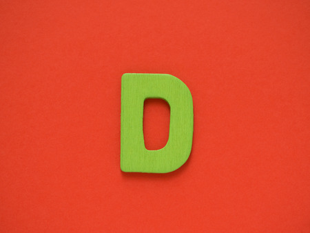 Capital letter D. Green letter D from wood on red background.