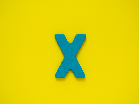 Capital letter X. Blue letter X from wood on Yellow background.