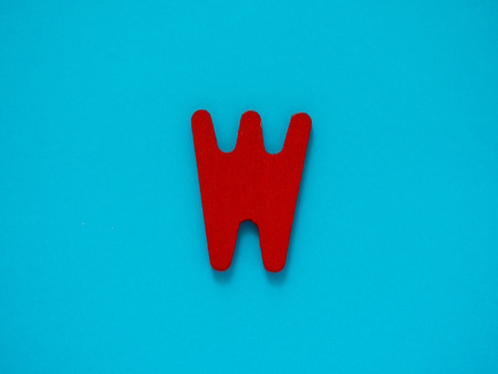 Capital letter W. Red letter W from wood on blue background. Stock Photo