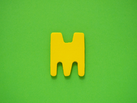 Capital letter M. Yellow letter M from wood on green background. Stock Photo