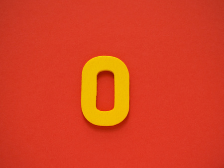 Capital letter O. Yellow letter O from wood on red background. Alphabet vowel.