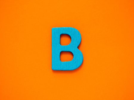 Capital letter B. Blue letter B from wood on orange background.