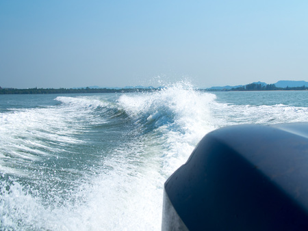 seaway: Restless foamy blue sea wake water on the sea water surface with clear blue sky while travel by speed boat in the ocean. Stock Photo