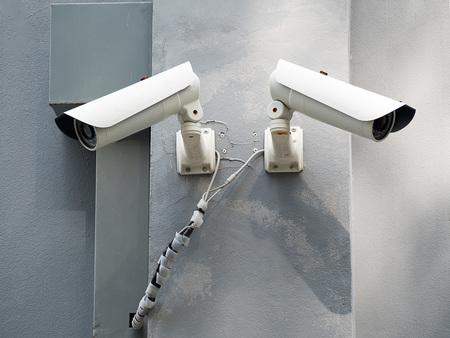 closed circuit television: White CCTV (Closed circuit TV) camera security monitoring on cement wall.