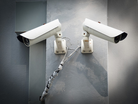 larceny: White CCTV (Closed circuit TV) camera security monitoring on cement wall.