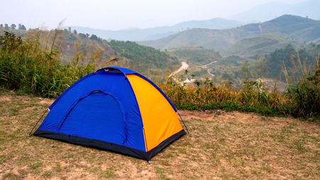 Blue and Yellow tourist camping tent in recreation area among meadow in mountain forest.