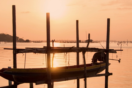 folk village: Long tail boat at beautiful sunset orange sky reflect with water lake at traditional folk fishing village in south Thailand. Stock Photo
