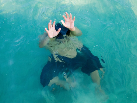 Drowning man in sea asking for help with raised his arms. Safety concept. Stock Photo