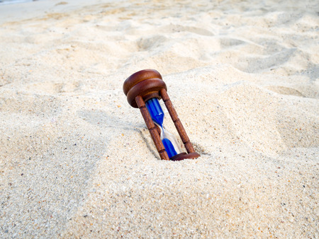 the passing of time: Hourglass on sand beach. Hourglass or Sand Timer measuring the passing time in a countdown to a deadline. Time concept.