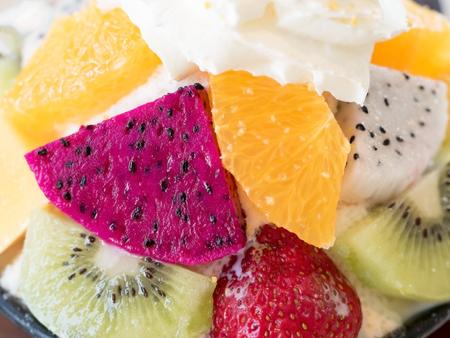bing: Closeup of fruits in Bingsu. Bingsu is local Korean shaved ice dessert serve with toppings such as chopped fruit, mango, orange, kiwi, strawberry, dragon fruit and berry syrup.