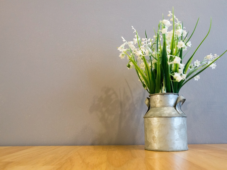 galvanized: White spring flowers in vintage galvanized vase on wood table and cement wall in background with copy space.