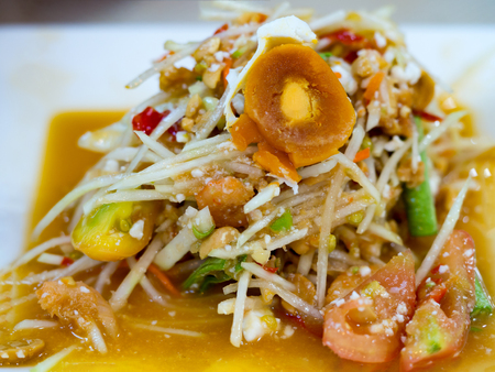 northeastern: Green papaya salad or Som tum with preserved egg. Popular Thai local food. Spicy salad from shredded unripe papaya, sliced tomatoes, raw yardlong beans, peanuts, dried mini shrimp, and fresh garlic.
