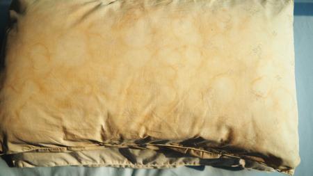침대에 타액에서 옅은 노란색과 갈색 색으로 더러운 베개 얼룩.