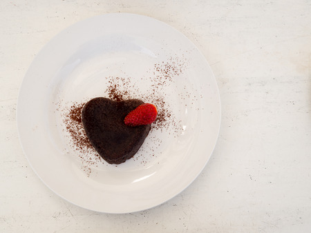 Warm chocolate lava cake in heart shape with strawberry in white plate on white table.