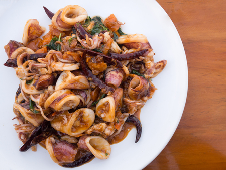 Stir Fried squid with salted egg york, seafood menu (local traditional Thai food) in white plate on wooden table. Stock Photo