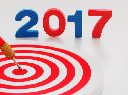 Year 2017 goal, two thousand seventeen with red bullseye dart arrow hitting target center dartboard in background. Happy New Year.