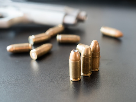 gunfire: 11mm bullets and short gun on black background. (selective focus)