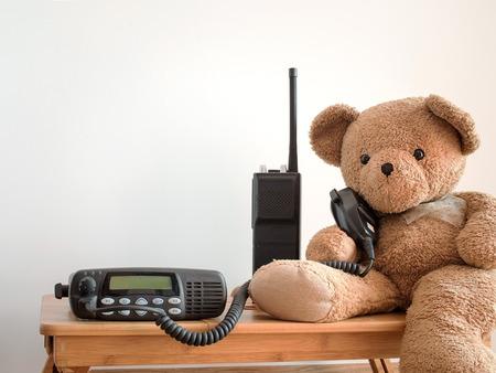 Cute bear holding speaker of black portable amateur radio for radio communication theme. Imagens