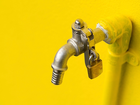 Yellow faucet on yellow wall with padlock prevent water theft. Concept of save water.