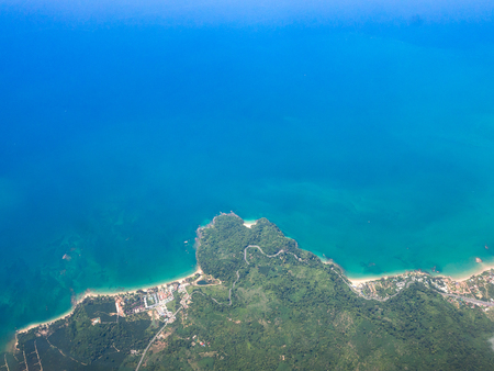Top view landscape Island mountain and coast with blue sea ocean. View from airplane while flying over Andaman sea in Thailand.
