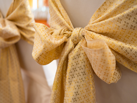 wedding chairs decorated yellow golden bow in wedding ceremony.