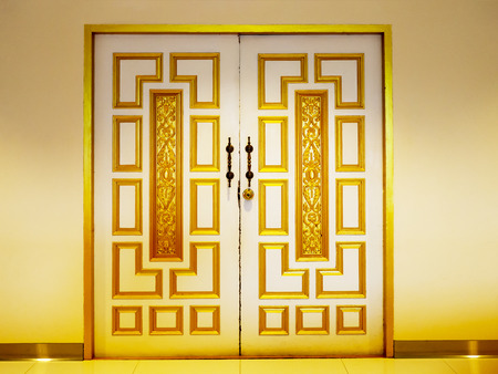 vintage gold door closed on white wall background.
