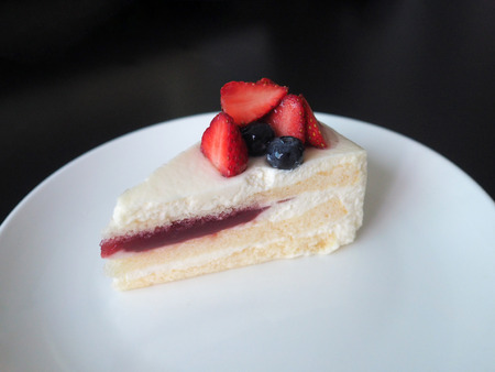 Strawberry cake dessert bakery with fresh strawberry and blueberry and strawberry jam on white plate.