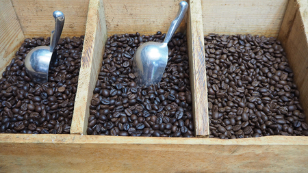 Three kinds of black coffee beans in crate with scoop.
