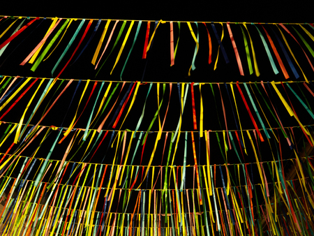Hanging colorful ribbons swaying in the wind at night for party celebration. Stock Photo - 122397908