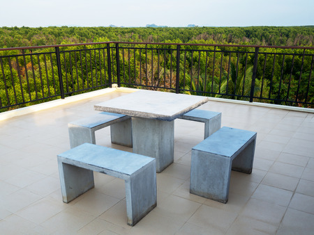 White marble bench table desk and marble chair on roof top with green natural mangrove view.