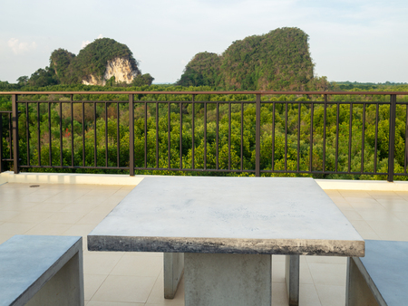 White marble bench table desk and marble chair on roof top with mountain hill and green natural mangrove view.