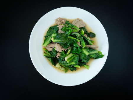Kale fried with pork in oyster sauce menu on white plate for meal with black background. Thai food.