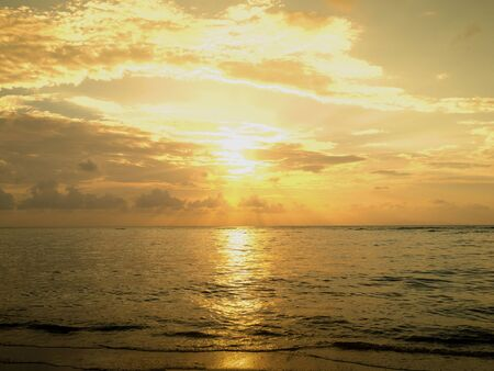 Amazing ocean sea sunset with orange yellow cloud and sky. Sunlight reflect with surface sea.
