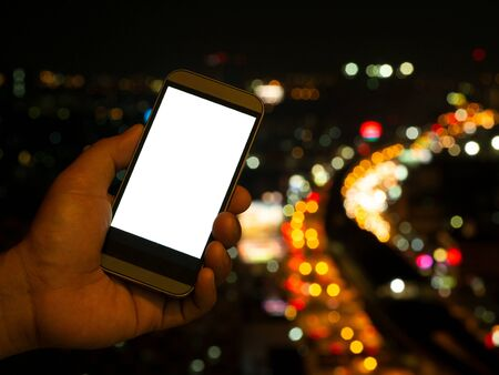 Man hand holding smart phone blank screen over light bokeh from road at night in city background.