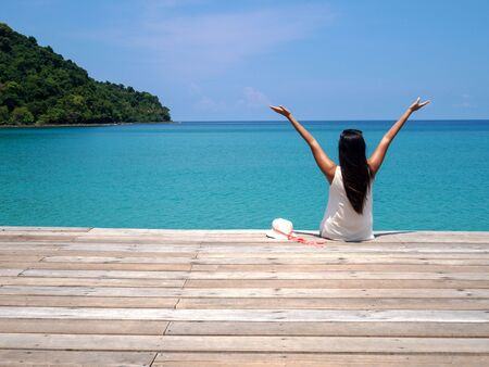 Young Asian woman with long black hair sitting on bench facing sea and raise her hands in sunny day for relax and enjoy vacation. Stock fotó