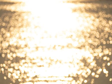 Abstract gold yellow bokeh of water surface reflect with sunset light.