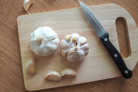 Organic garlic cloves and garlic bulb on wood chopping board. Concept healthy lifestyle.