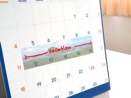 Red vacation write on white calendar marked for remember and target time to long vacation and relax time with ocean and Island background.