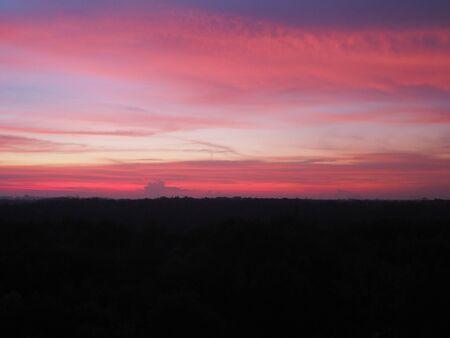 Silhouette sunset sky background. Twilight natural sunset sunrise over forest mountain. Warm color sky orange blue purple. Stock fotó