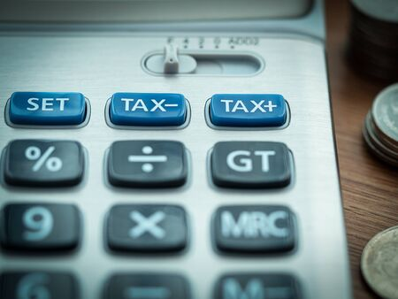 Tax cuts or reduce and tax increase concept, selective focus on TAX minus and TAX plus buttons on calculator with background of blurred coins.
