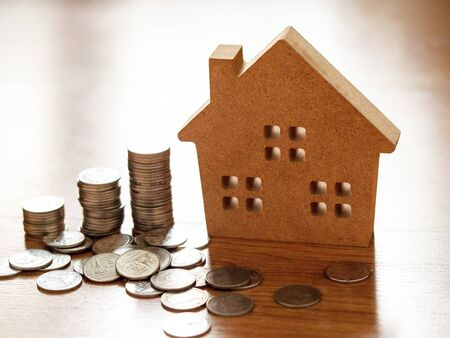 Home loan. Buy and sell houses and real estate. Business concept save money for home. Brown wooden home model with coins.