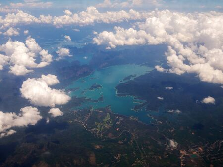 Top view landscape Island mountain and coast with blue sea ocean and white clouds. View from airplane while flying over Andaman sea in Thailand.